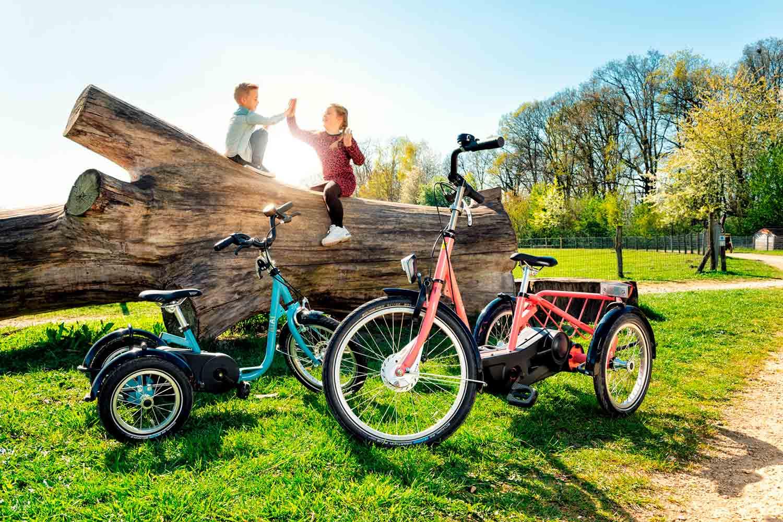 Dos niños jugando cerca de sus triciclos