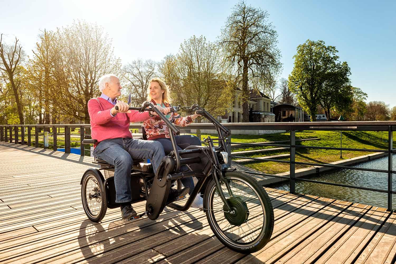 Personas joven con persona mayor pedaleando juntos el triciclo tandem Orthros